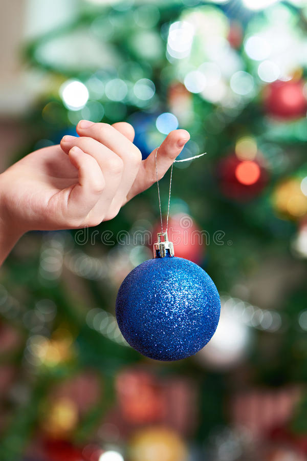 Children`s hand with blue Christmas toy ball. Close up royalty free stock images