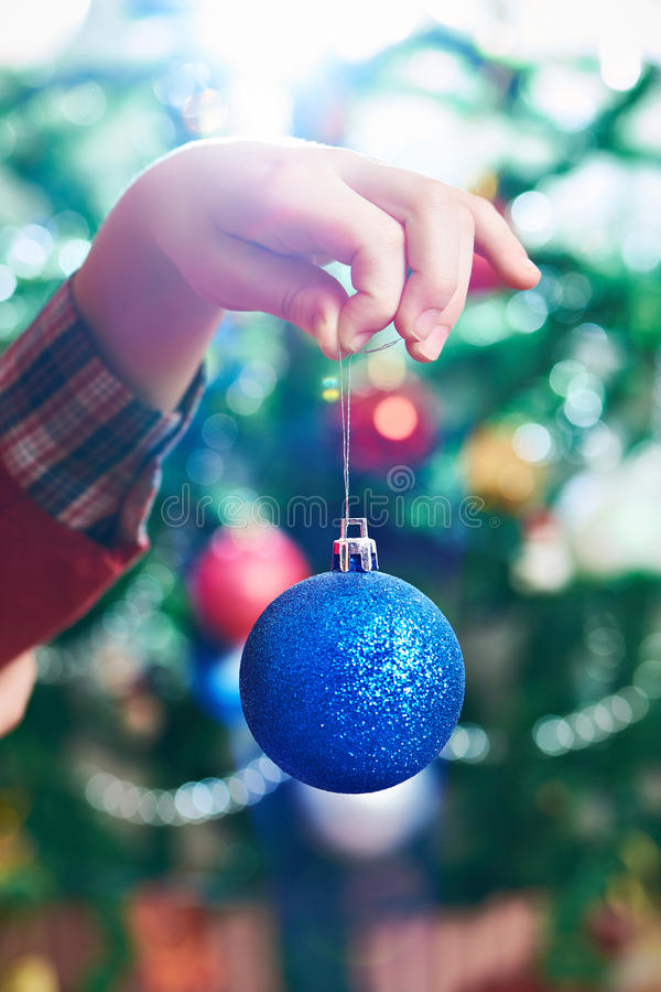 Children`s hand with blue Christmas toy ball. Close up royalty free stock image