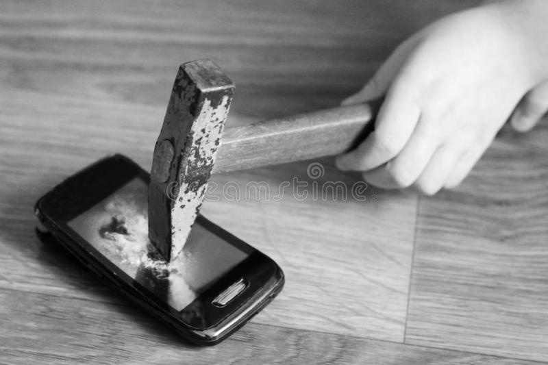 Children`s hand with a hammer breaks the smartphone, black and white royalty free stock photography