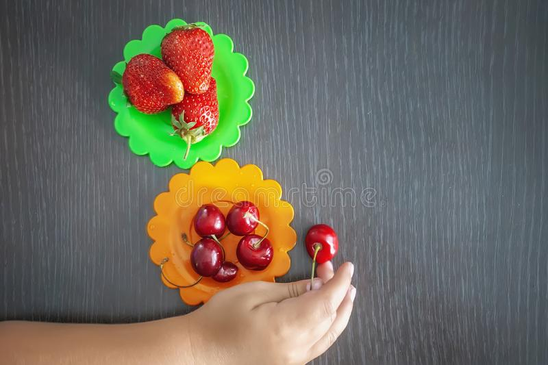 Children`s hand holding strawberries and cherries on a wooden background, colored plates of cherries and strawberries. The concep. T of healthy eating in the stock photo