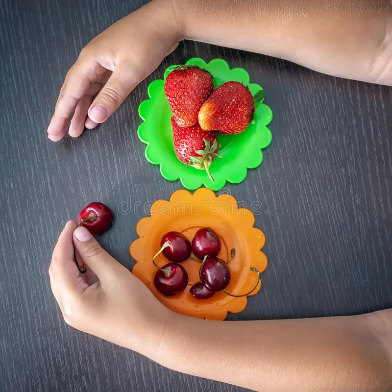 Children`s hand holding strawberries and cherries on a wooden background, colored plates of cherries and strawberries. The concep. T of healthy eating in the stock photography
