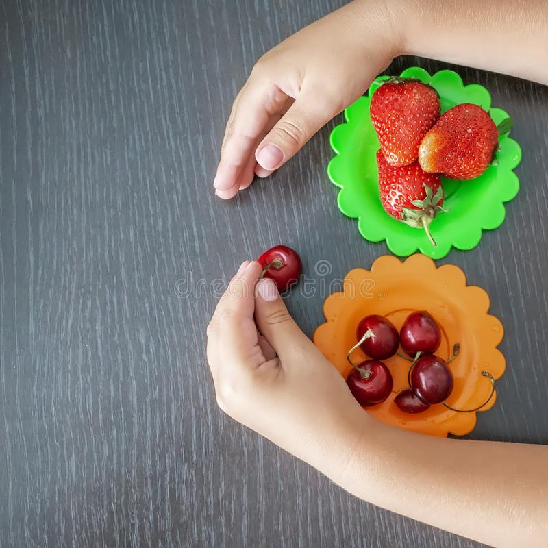 Children`s hand holding strawberries and cherries on a wooden background, colored plates of cherries and strawberries. The concep. T of healthy eating in the royalty free stock images