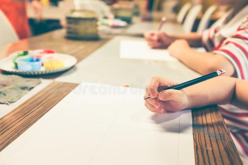 Children`s hand prepare drawing on art class. Vintage film filte. Children`s hand prepare writing or drawing with pencil on paper at art class. Strengthen the royalty free stock photos
