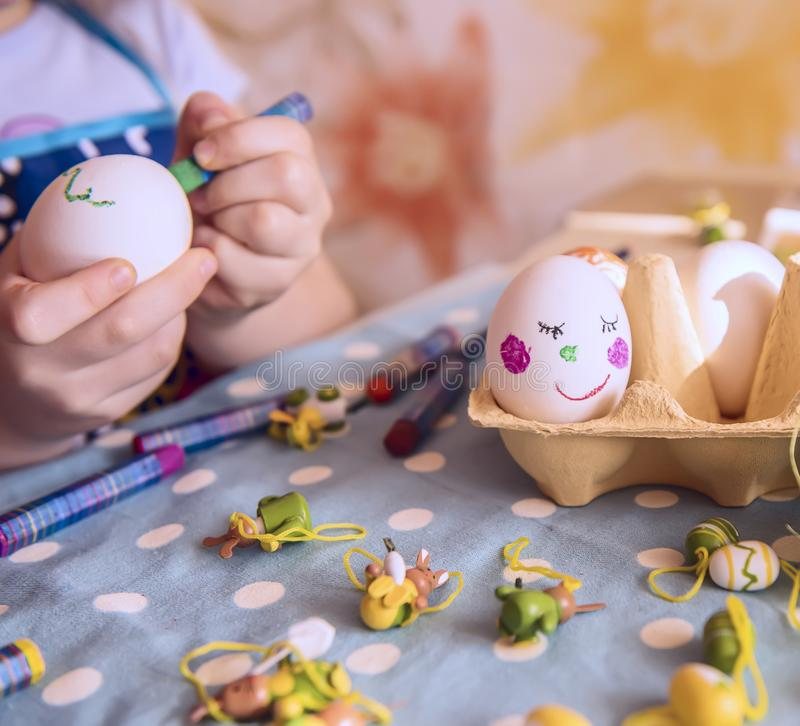 Children`s handles decorate eggs for Easter. royalty free stock image