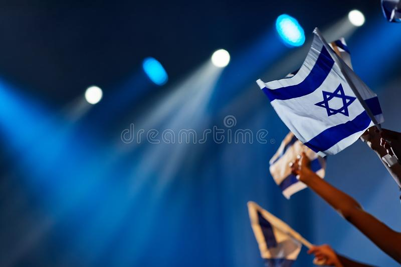 Children`s hands at a concert hold the flag of Israel against the background of blue rays of lighting stock photo