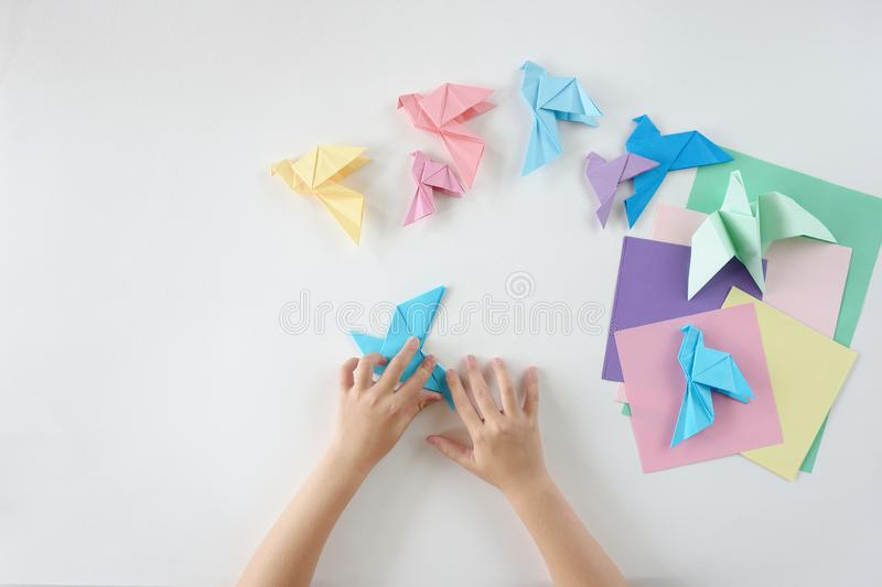 Children`s hands do origami from colored paper on white background. lesson of origami stock image