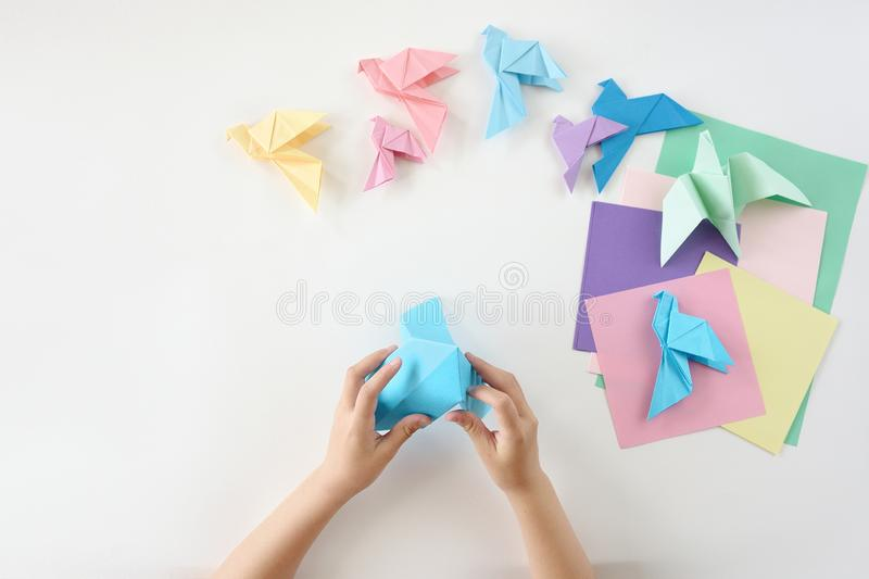 Children`s hands do origami from colored paper on white background. lesson of origami stock photo