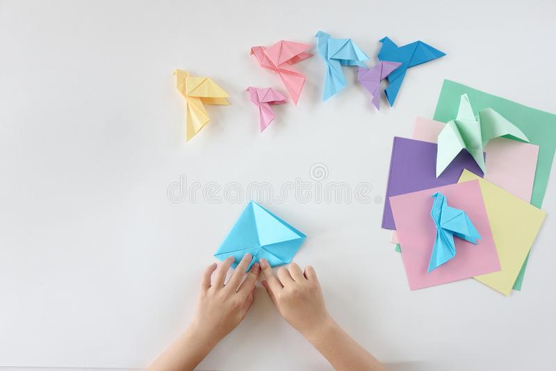Children`s hands do origami from colored paper on white background. lesson of origami stock photos