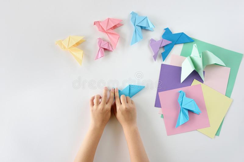 Children`s hands do origami from colored paper on white background. lesson of origami royalty free stock photos