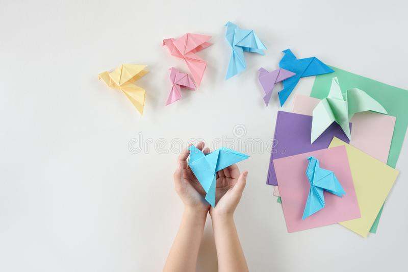 Children`s hands do origami from colored paper on white background. lesson of origami royalty free stock images