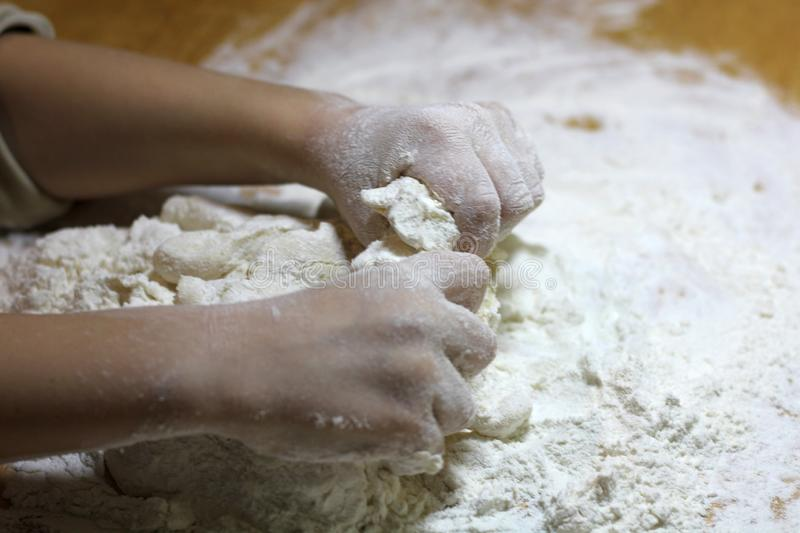 Children`s hands and dough. Little boy kneading a dough. Healthy handmade food concept. bakery products, pizza, flour. cooking. Workshop. baby`s hands roll out stock image