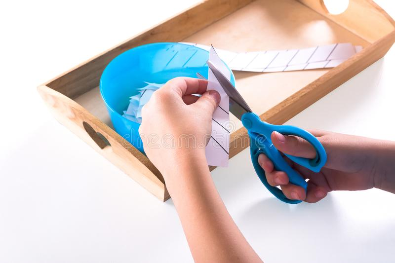 Children`s hands hold blue scissors and cut the paper. On a wooden tray are Montessori materials for a lesson stock photos