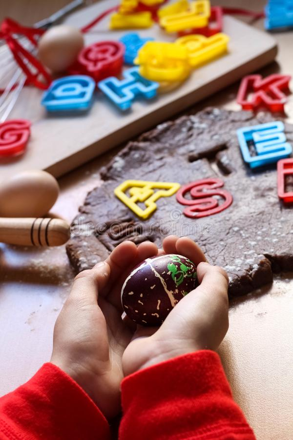Children`s hands hold a decorated Easter egg. Cooking traditional Easter biscuits. Easter eggs. Easter food concept royalty free stock images