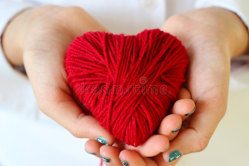 Children`s hands hold a heart of red thread for knitting. Valent royalty free stock photo
