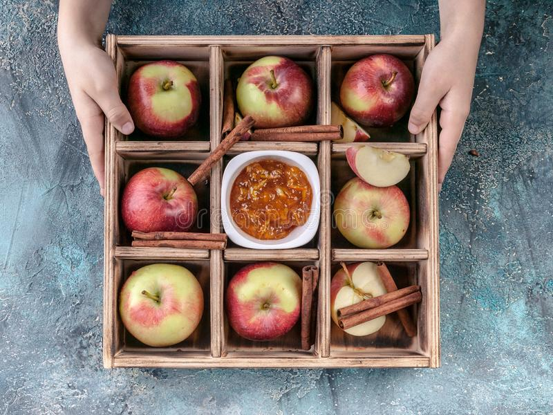 Children`s hands hold ripe apples, cinnamon, jam in a plywood box on a blue concrete background stock images