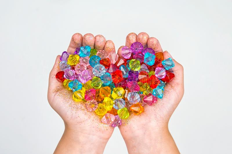 Children`s hands, hands holding beads on a white background stock photos