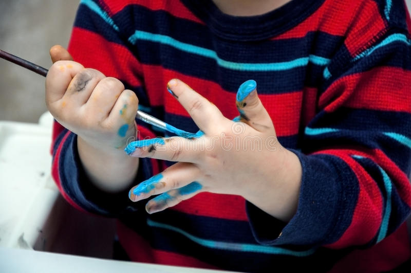 Children`s hands holding a brush with blue paint royalty free stock image