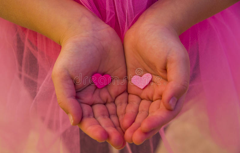 Children`s hands holding the heart on a pink background. Concept of love, care, faith, hope, purity. stock image