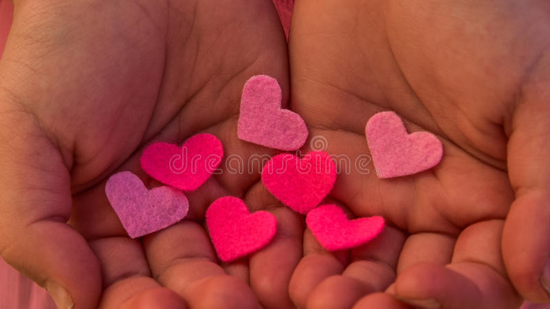 Children`s hands holding the heart on a pink background. Concept of love, care, faith, hope, purity. stock images