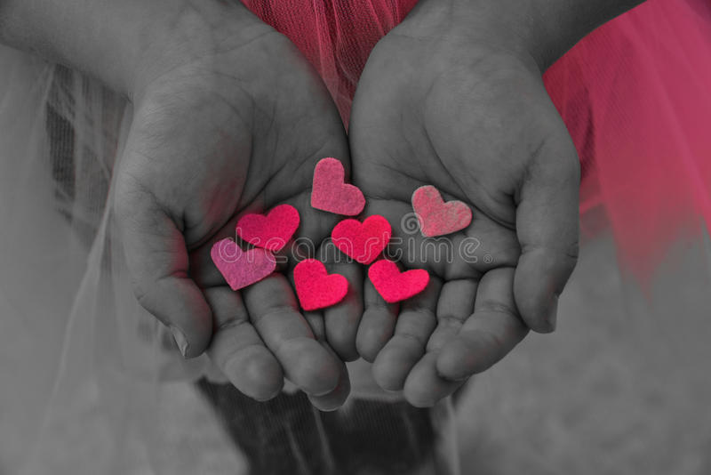 Children`s hands holding the heart on a pink background. Concept stock photos