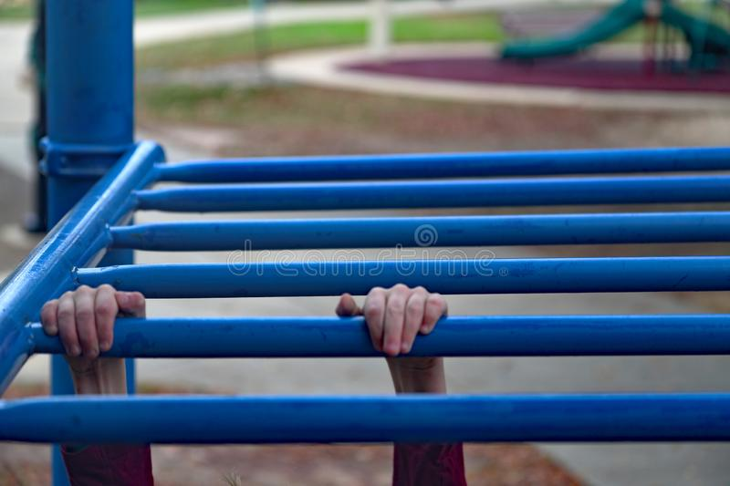 Children`s hands on monkey bars. Children`s hands gripping monkey bars while playing at the playground stock photo