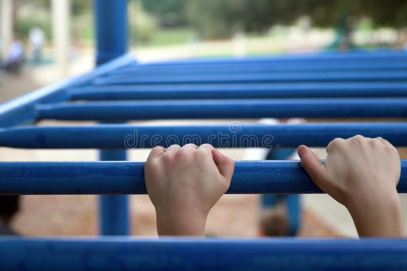 Children`s hands on monkey bars. Children`s hands gripping monkey bars while playing at the playground stock photos