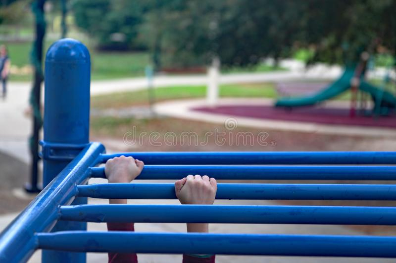 Children`s hands on monkey bars. Children`s hands gripping monkey bars while playing at the playground royalty free stock photo