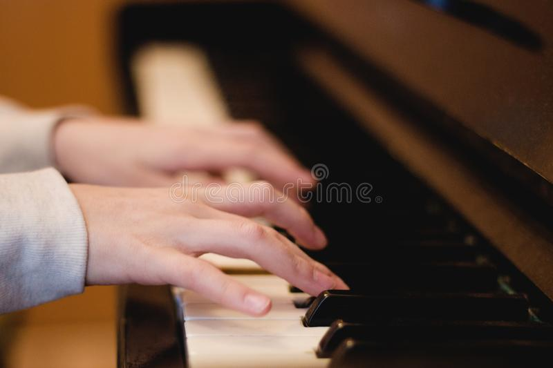 Children`s hands on the piano keys, rehearsal music, learning to play the piano.  stock images