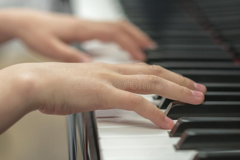 Children`s hands are playing the piano. Child`s hand on piano keys. stock photos