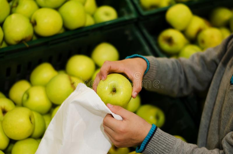 Children`s hands put apples in a bag of cotton at the supermarket. Reusable environmental shopping bag. Zero waste concept stock images