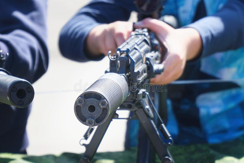 Children's hands on a rifle or machine gun royalty free stock image