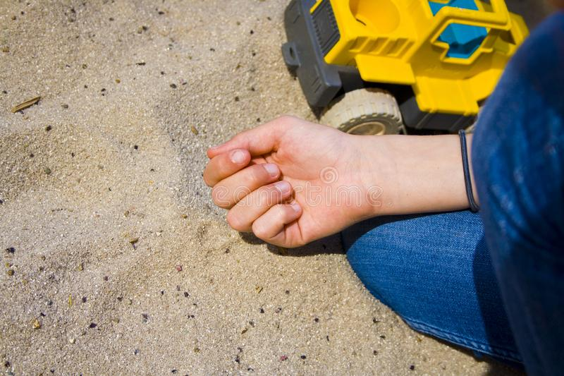 Children`s hands in the sand while playing. stock photos