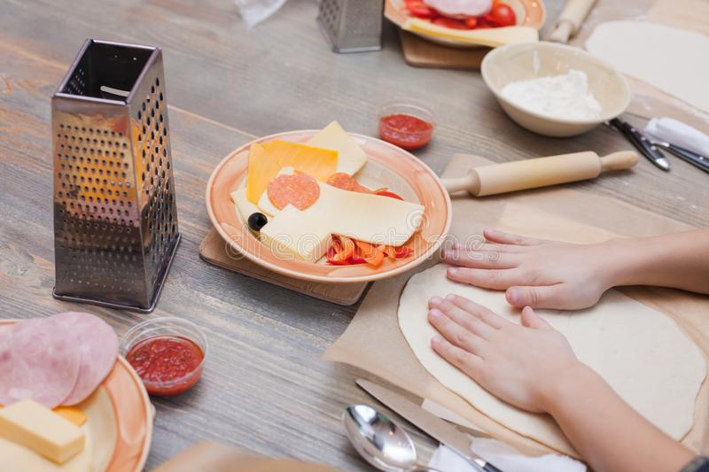 Children`s hands smoothen dough for pizza on a wooden table, children`s cooking lesson. royalty free stock images