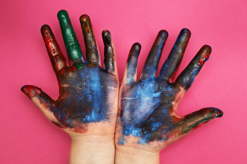 Children`s hands are stained with a multicolored paint on a pink background.  royalty free stock image