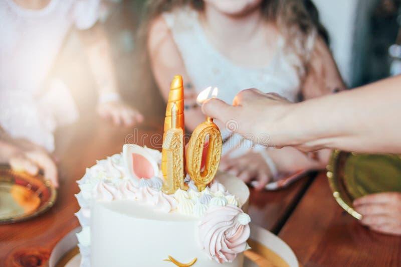 Children& x27; s-handsmå flickor att nå för kakan Stor härlig kakaenhörning på de tio åren födelsedag av den lilla prinsessan på royaltyfria foton