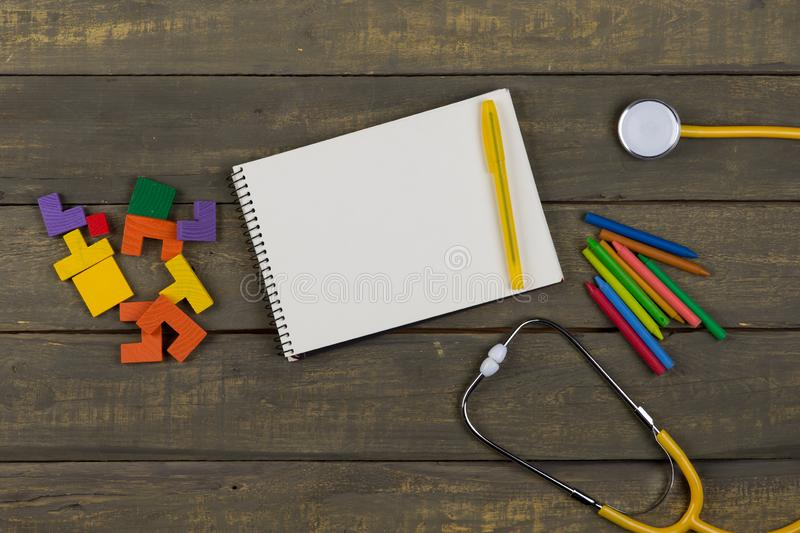 Children's healthy development concept - blank notepad, yellow stethoscope, colorful wooden jigsaw puzzles, crayons. On wooden background, baby, care stock photography