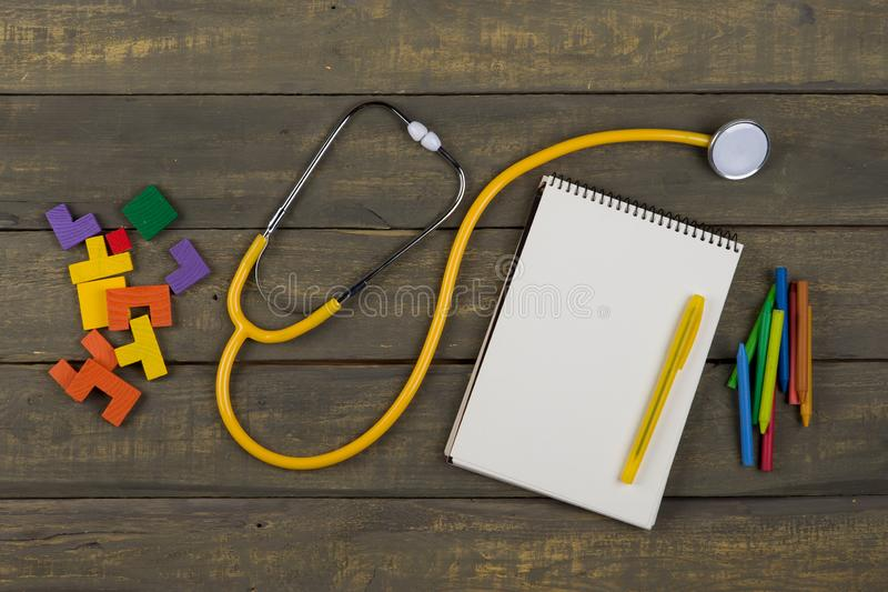 Children's healthy development concept - blank notepad, yellow stethoscope, colorful wooden jigsaw puzzles, crayons. On wooden background, baby, care royalty free stock photography