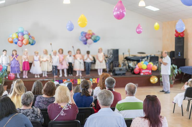 Children's holiday in kindergarten. Children on stage perform in front of parents. image of blur kid's show on stage at school. For background usage. Blurry stock photography