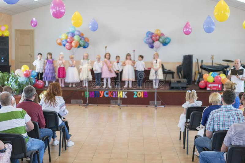 Children's holiday in kindergarten. Children on stage perform in front of parents. image of blur kid's show on stage at school. For background usage. Blurry royalty free stock image