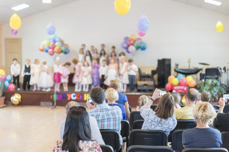 Children`s holiday in kindergarten. Children on stage perform in front of parents. image of blur kid `s show on stage at. School , for background usage. Blurry royalty free stock photo