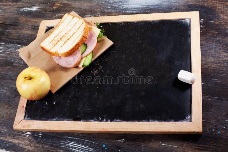 Children& x27; s lunch aan schoolraad, krijt, een ruimte voor inschrijving, appel, sandwich stock afbeeldingen