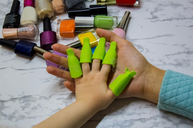 Children`s manicure. Children`s beauty salon. Paint your child`s nails with nail Polish. Nail Polish remover clips on the girl stock photo