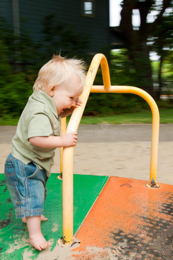 Children's Merry-Go-Round. A young boy plays on a merry go round while it is spinning royalty free stock photography