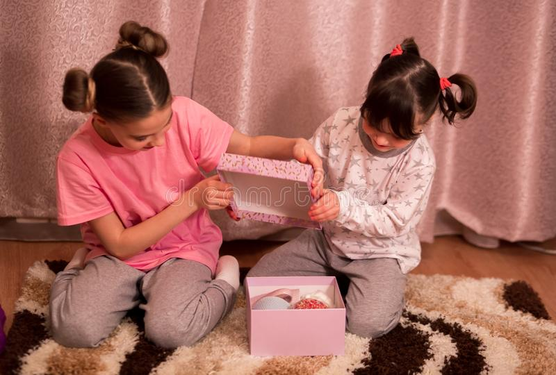 Children`s pajama party. funny girls in pink, white and gray pajamas with bob hairstyles open a surprise gift box with sweets stock image