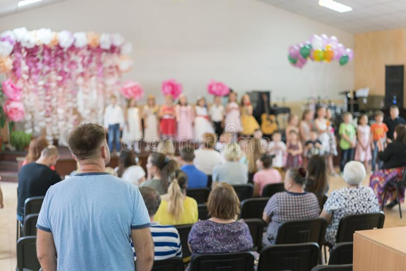 Children's party in primary school. Young children on stage in kindergarten appear in front parents. blurry. back to school royalty free stock image