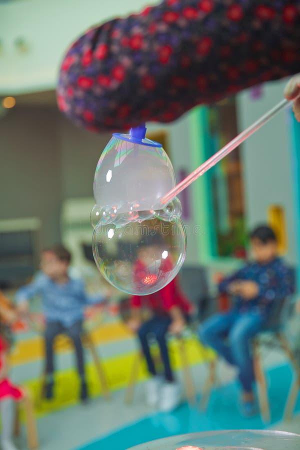 Children`s party. To burst the soap bubble . Soap bubbles show. royalty free stock image