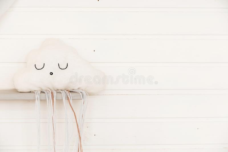 Children`s pillow in the shape of a cloud on the background of a wooden wall royalty free stock photos