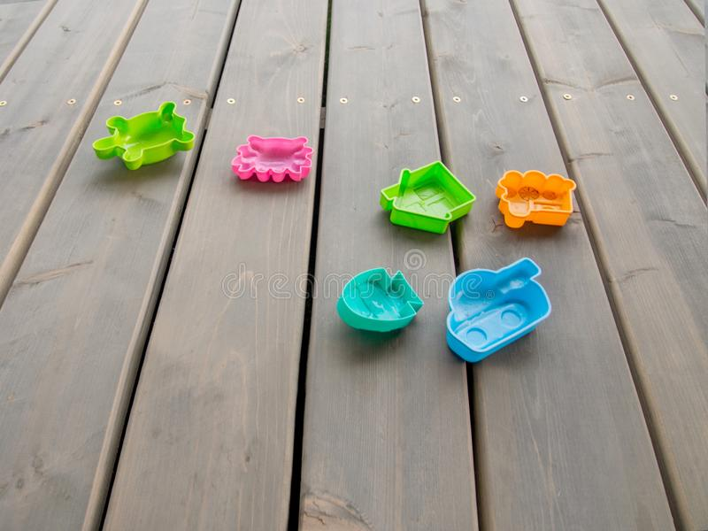 Children`s plastic toys of different colours on the wooden floor on the terrace of a country house. Horizontal orientation, space. For text royalty free stock photo