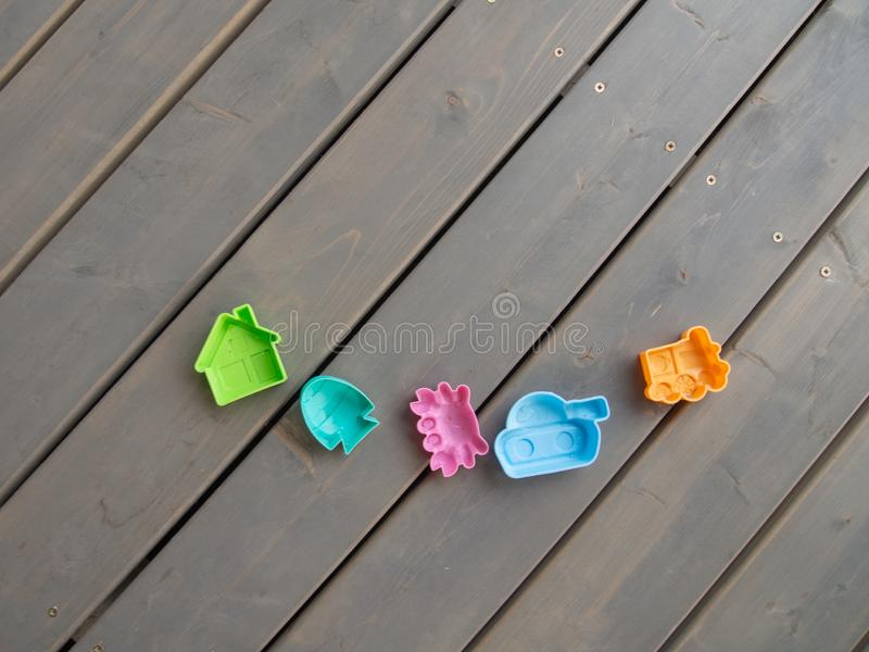 Children`s plastic toys of different colours on the wooden floor on the terrace of a country house. Horizontal orientation, space. For text stock image