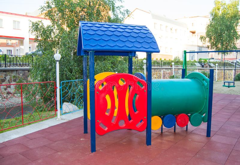 Children`s Playground with funny train made of multi-colored plastic and metal material, entertainment for children outdoors in stock images